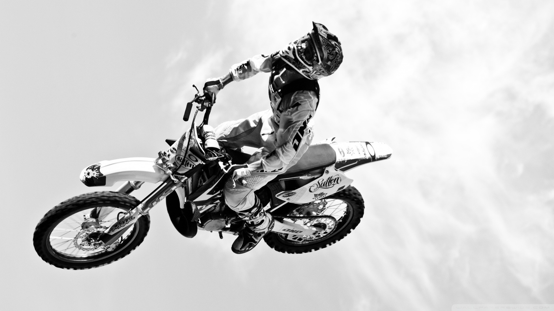 dirtbike moto vehicles motorcycle motorbike bike flight fly black white wheels people uniform sky clouds extreme sports racing cross