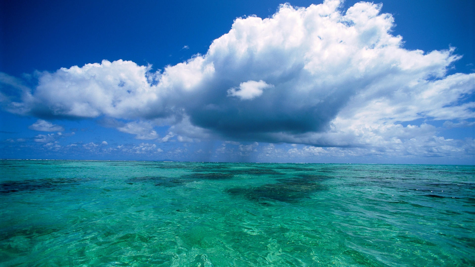 Fluffy clouds over clear ocean