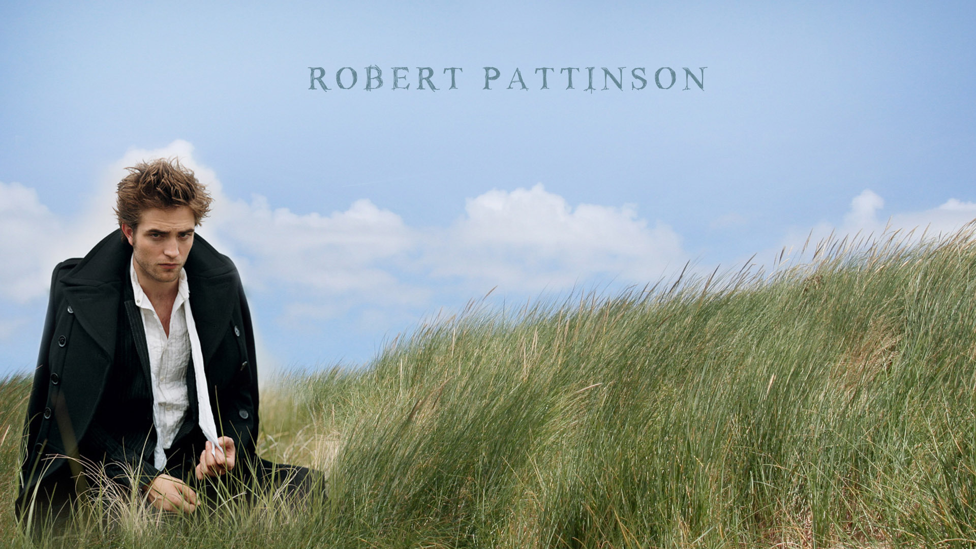 Robert Pattinson sitting in the grass