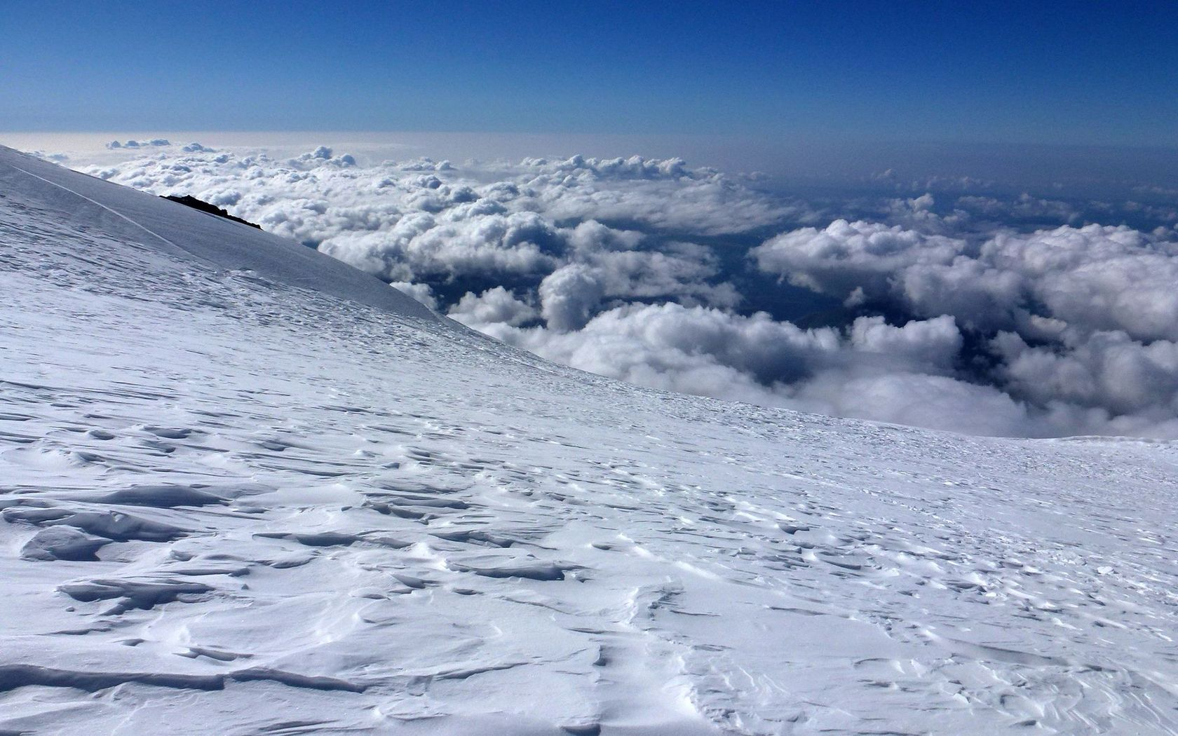 Snowy mountain peak above the clouds