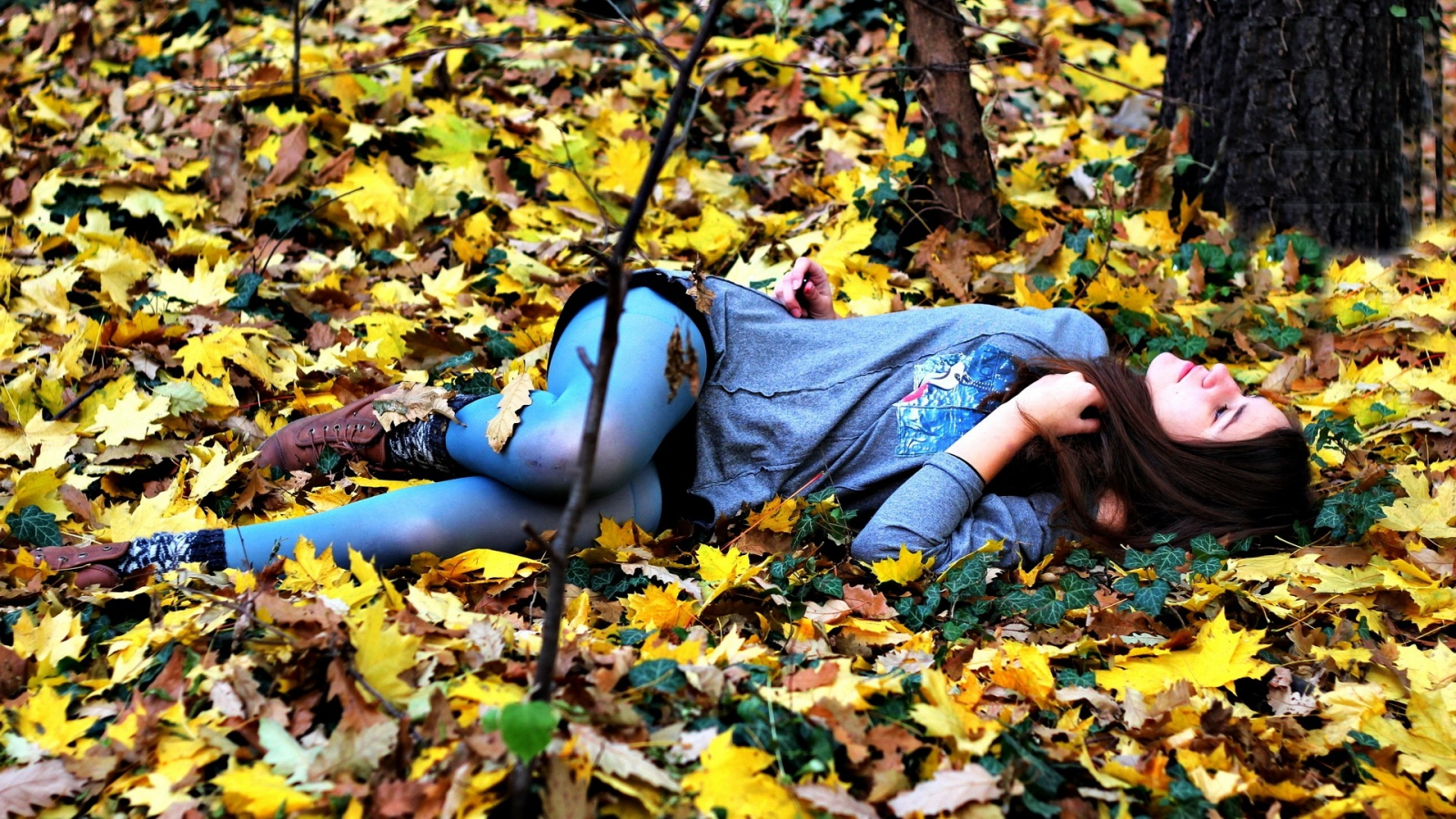 Woman lying in fall leaves